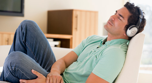 Man listening to headphones on couch